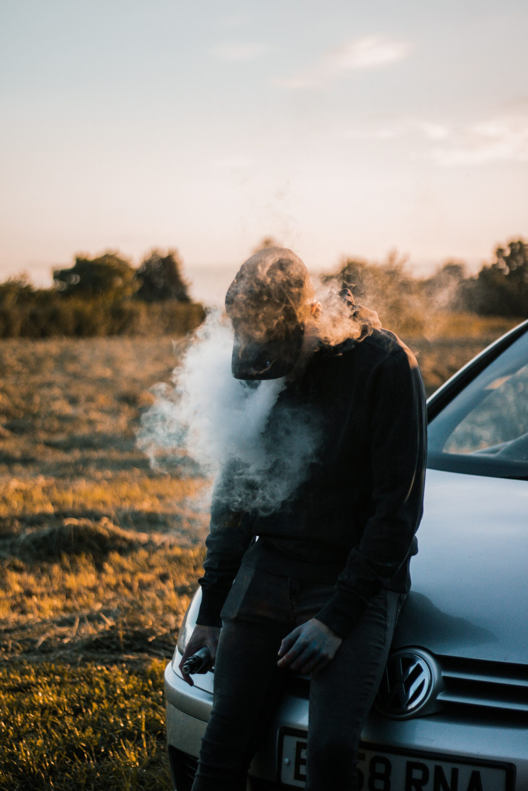 boy vaping sitting on car