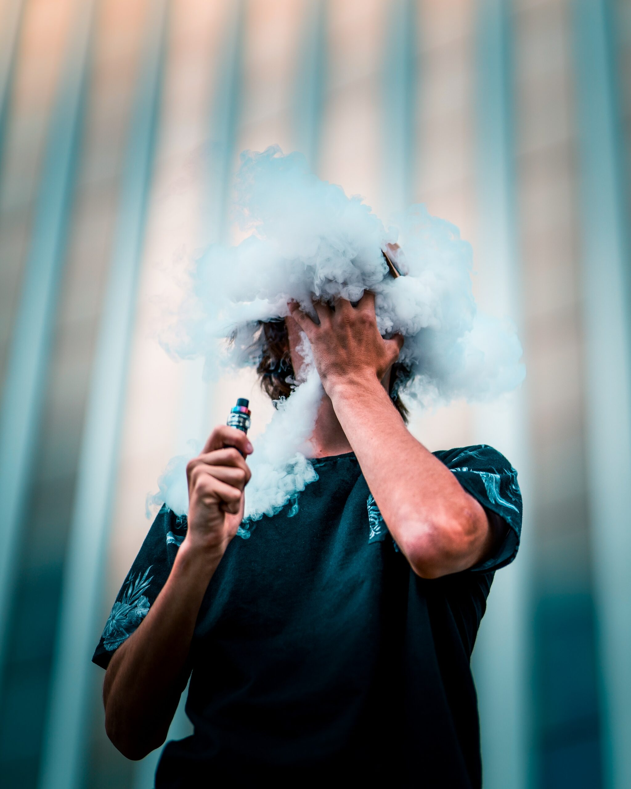 a man vapes cannabis and his head is in the clouds